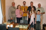 Athol Macgilchrist, Siegrun Macgilchrist with blitz trophy, Dr. Kenny Brooksbank giving back the championship trophy, Charlie Roy, joint winner of the Robertson cup, Steell MacFadzean, founder member & president. Ali with league trophy & Zak, youngest member of the club.